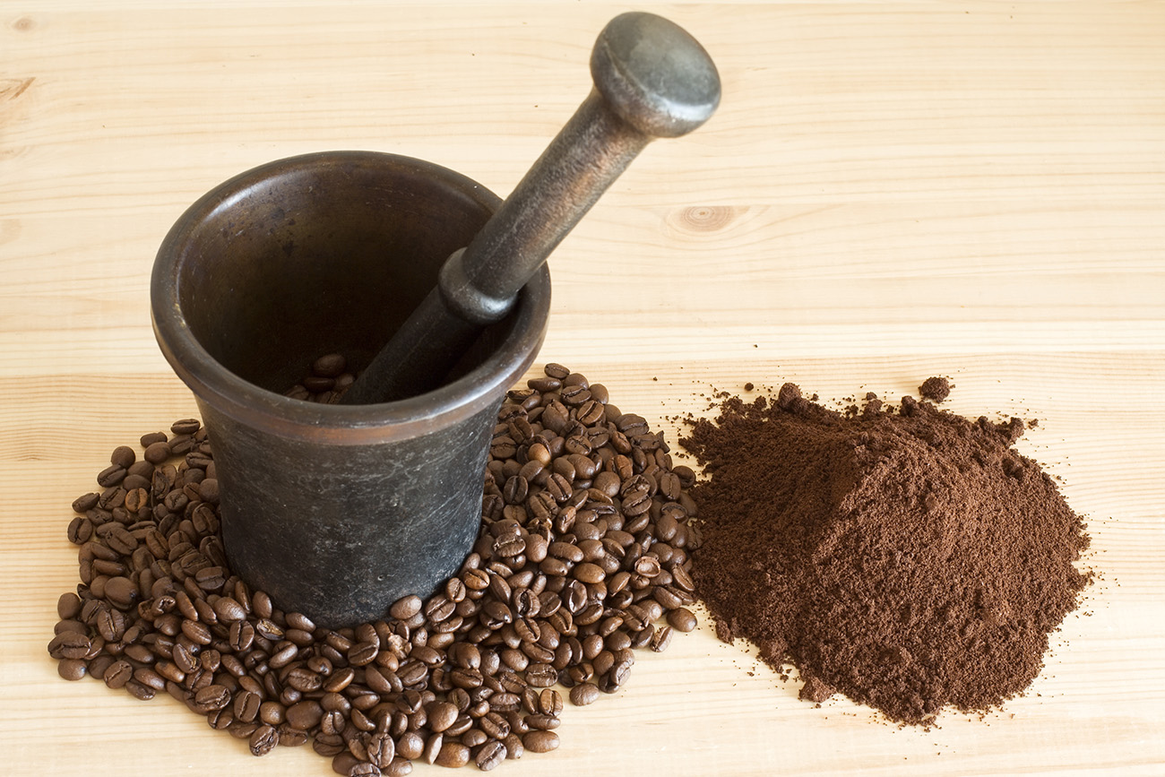 Coffee beans on wooden bowl with pestle 50551