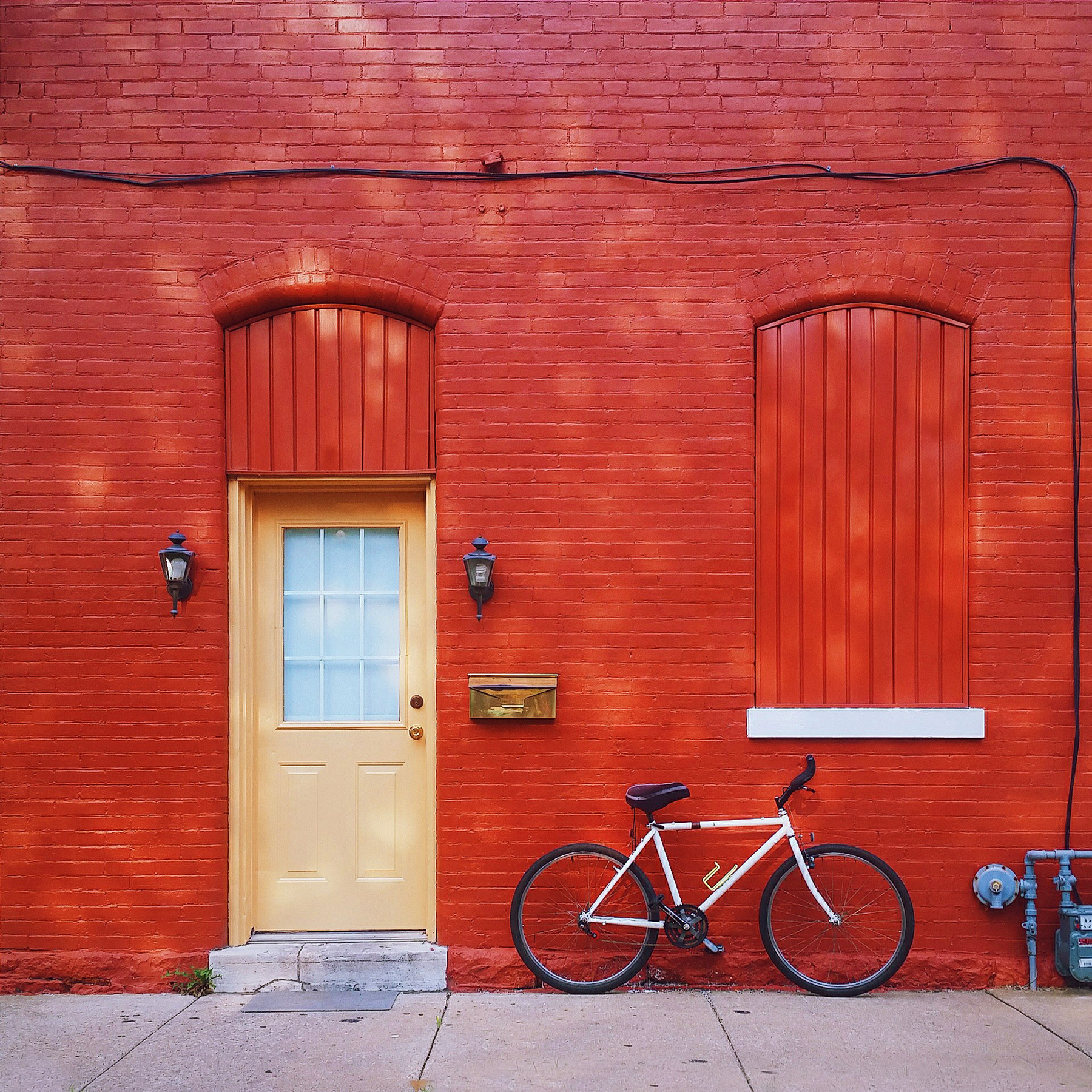 Bicycles parked against a red wall 52273