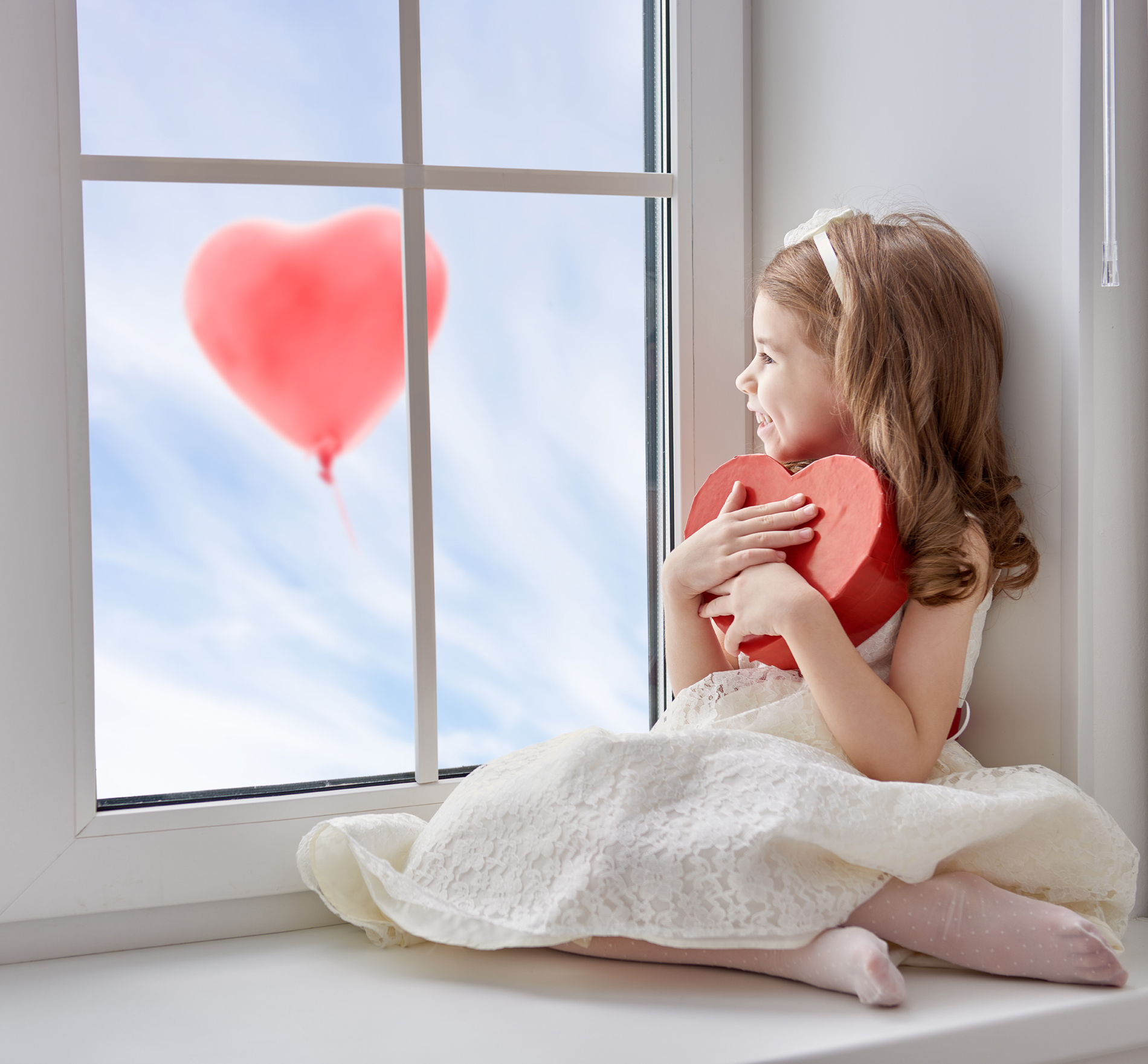 Little girl holding heart-shaped gift box 52776