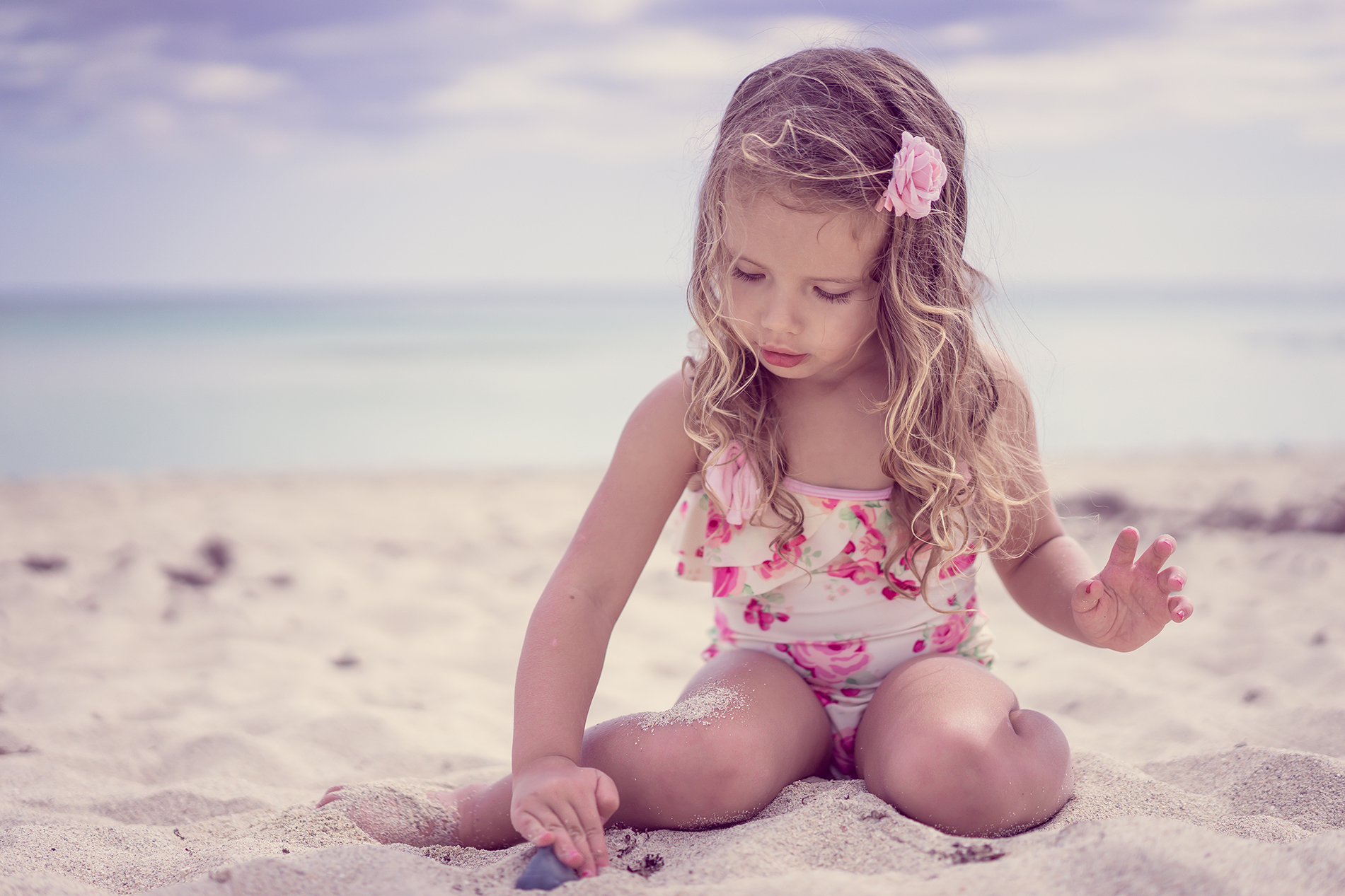 Little girl playing with sand on the beach 53774