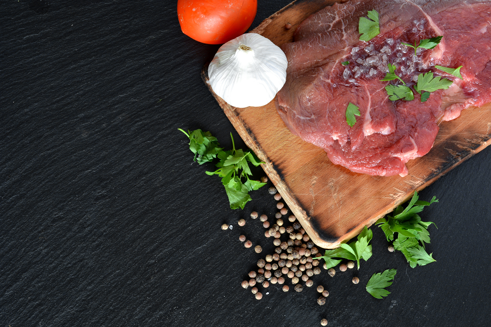 Pepper and fresh meat on a chopping board  53942