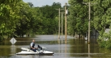 A man uses a jetski to travel between his home and Osage City, after Missouri was affected by severe flooding 44355