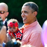 President Obama holds a baby as he greets members of the military and their families during a Fourth of July celebration on the White House's South Lawn. 44947